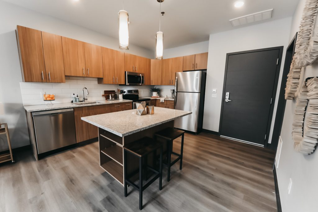 Modern kitchen with wood flooring - Six Canyon Apartments